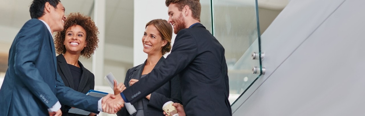 Multi-ethnic men in hard hats talking in manufacturing plant