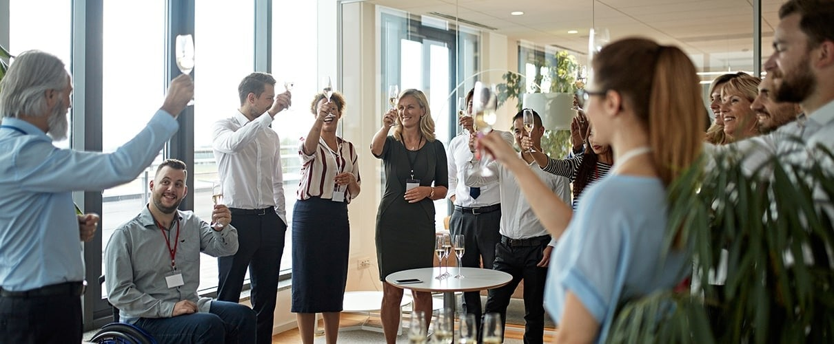 Wide angle view of mature male CEO and diverse business colleagues holding up champagne in preparation for celebratory toast at business event.