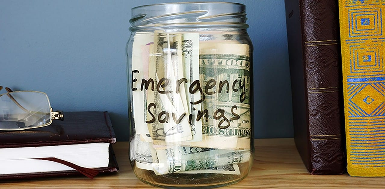 Jar on bookshelf with emergency savings cash