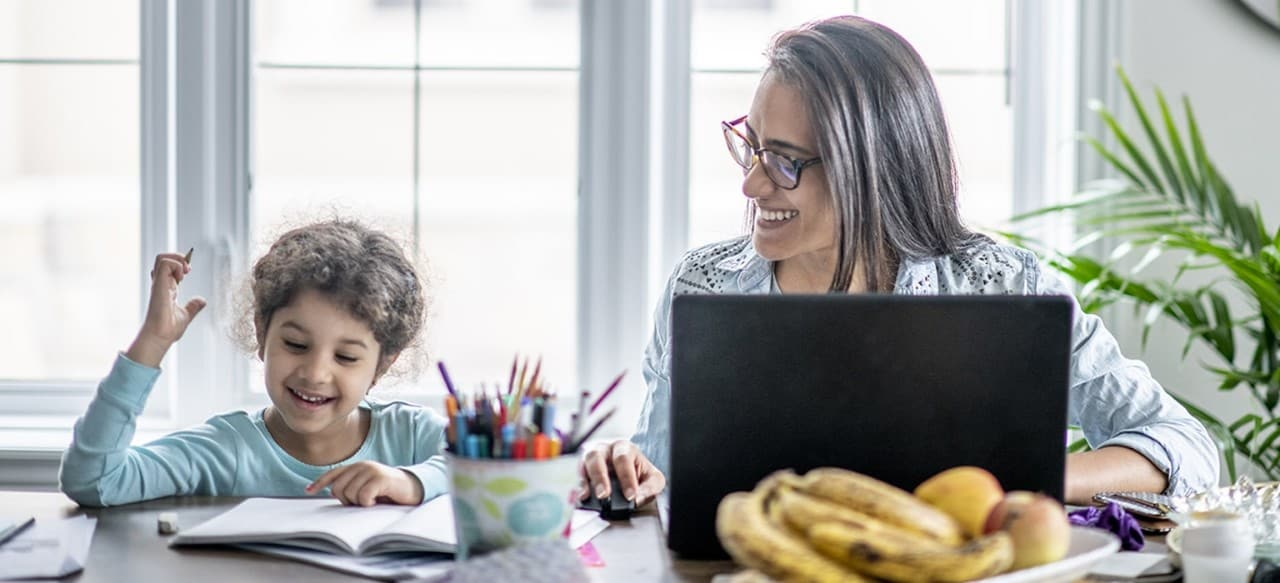 Mother working on laptop sitting next to daughter doing schoolwork