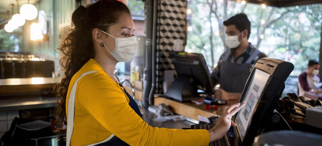Female restaurant cashier wearing mask using register with male masked employee in background