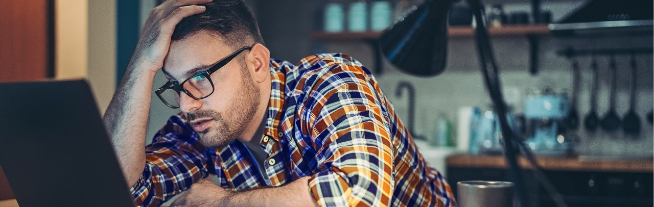 Frustrated man looking at computer with hand on his head
