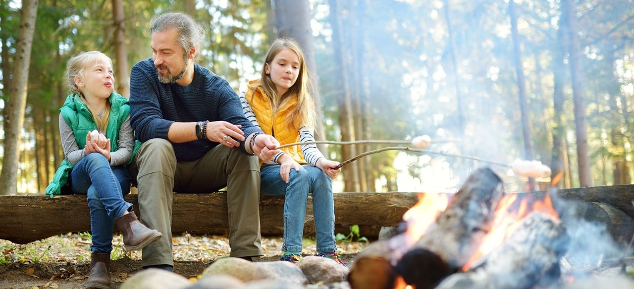 Father at campsite with two young daughters roasting marshmallows in fire pit