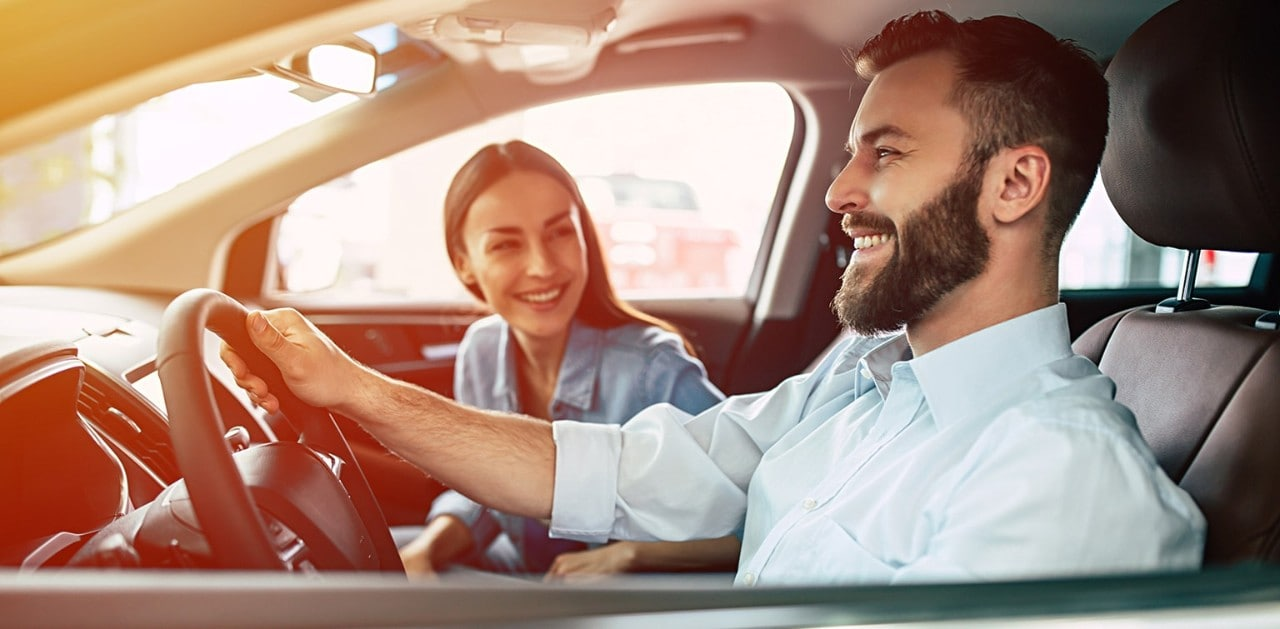 Happy, young couple driving new car