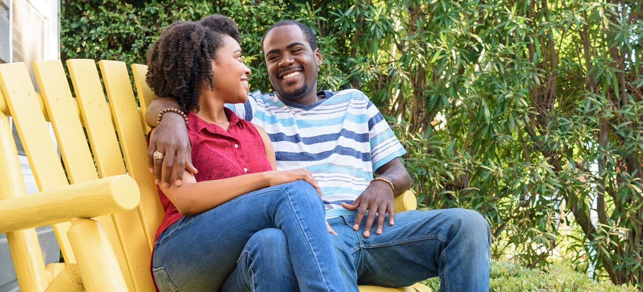 African-American couple sitting on Adirondack bench in yard