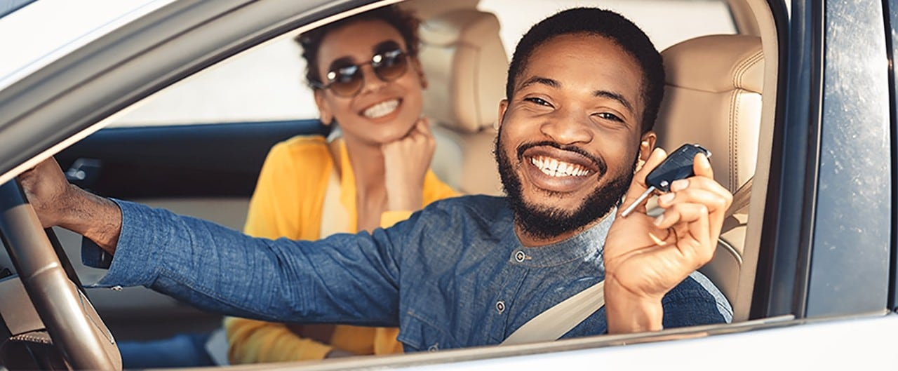 Happy African-American couple sitting in new car holding keys