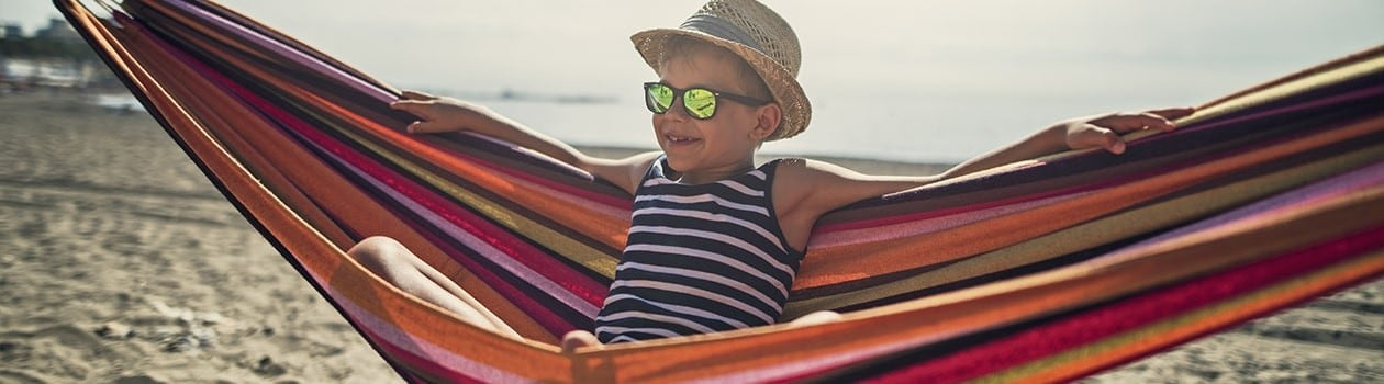 Young child wearing hat and sunglasses sitting on hammock at the beach