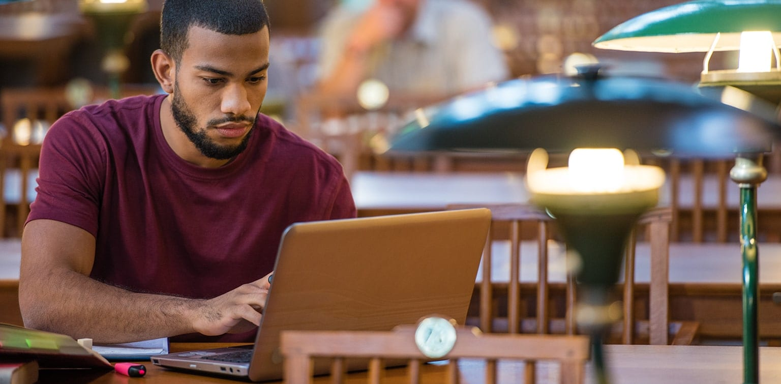 African-American man sitting at library table using laptop