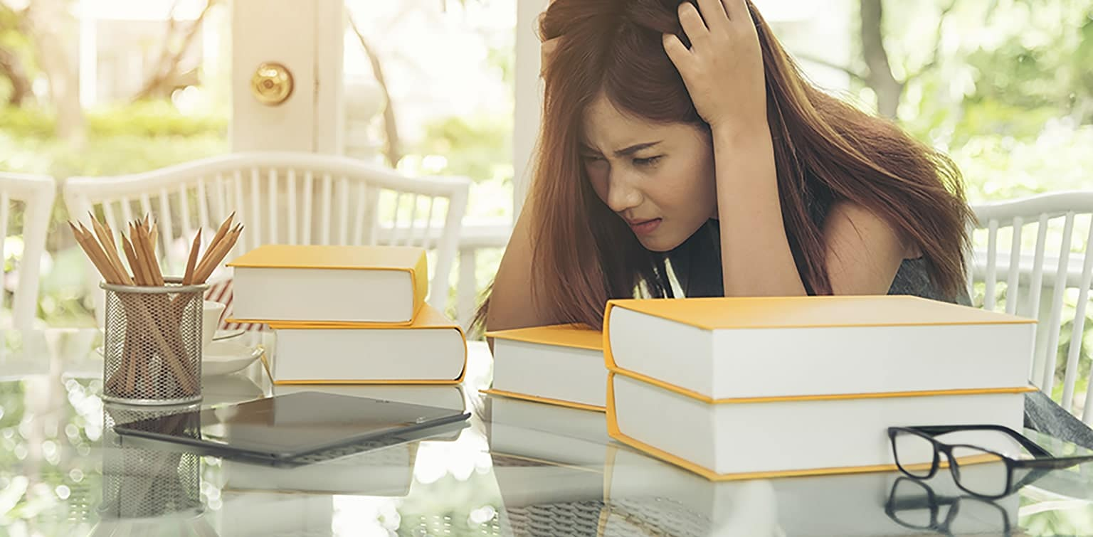Asian woman with head in hands looking at stack of books