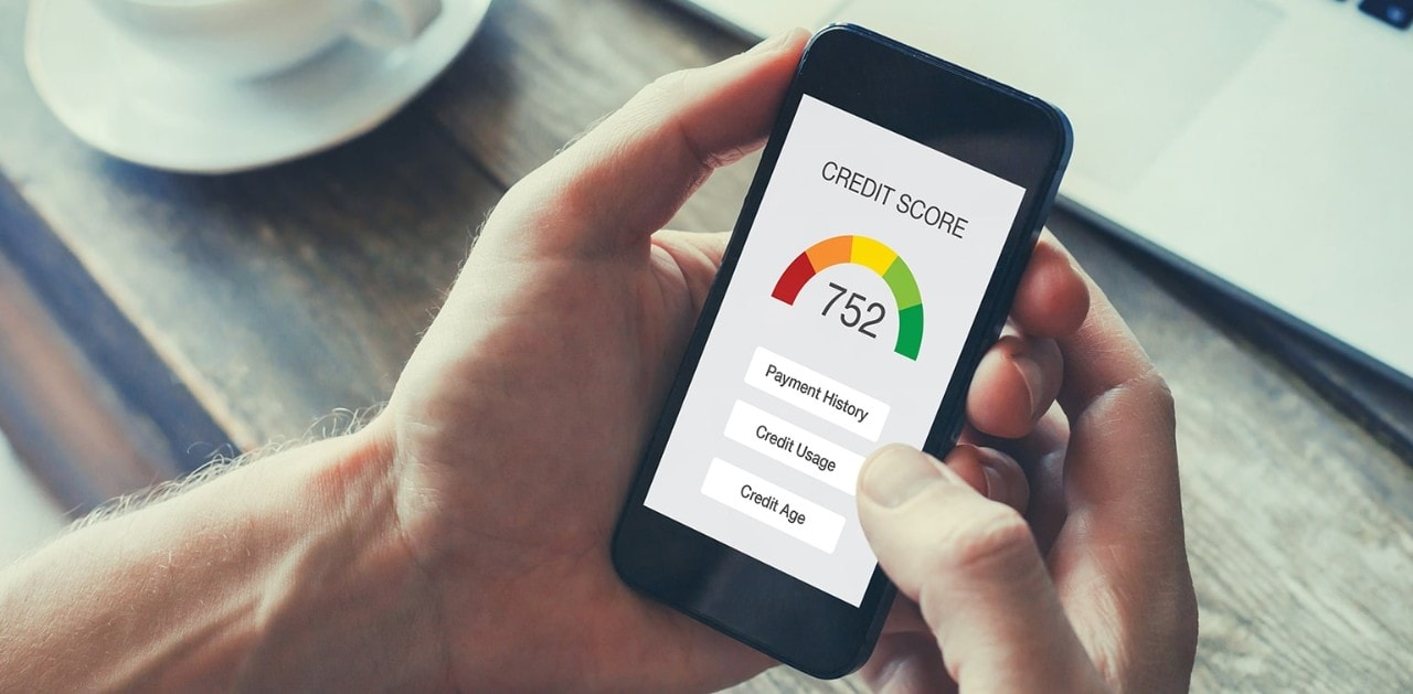 Man holding smartphone showing credit score