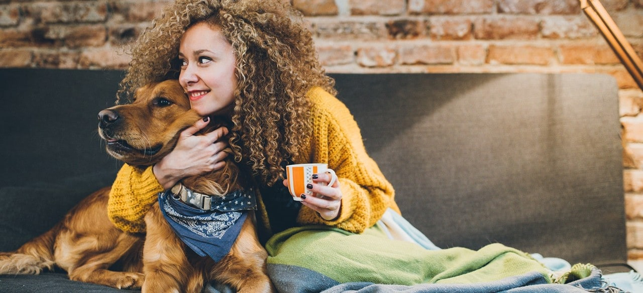 Woman snuggling with dog on couch