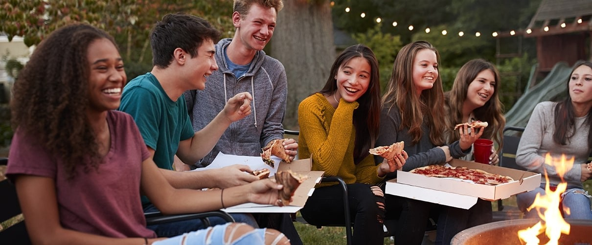 Diverse group of young friends eating take-out pizza in backyard