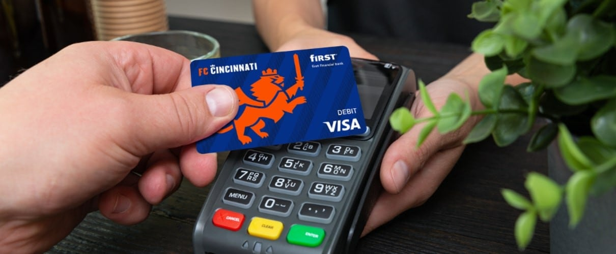 Man using First Financial Bank's contactless payment feature for a purchase.