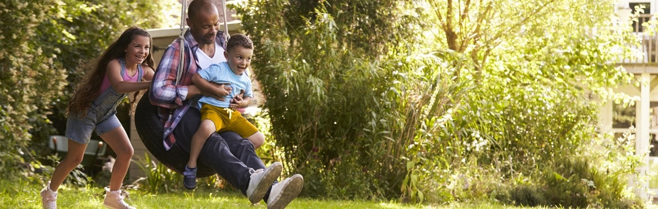 African-American girl pushing father and young brother on tire swing