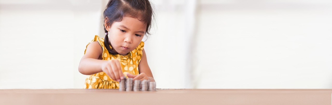 Young Asian girl stacking coins