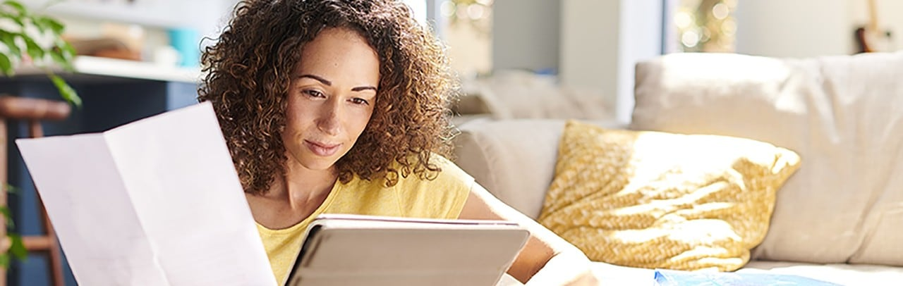 African-American woman holding financial paper and looking at tablet