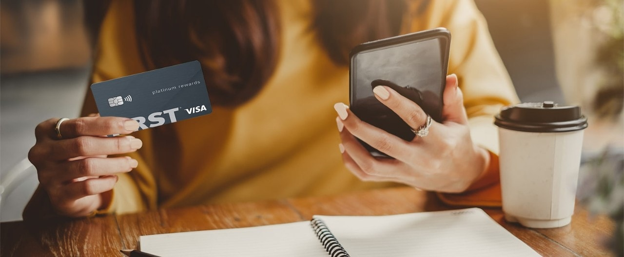 Asian woman holding First Financial credit card and looking at smartphone